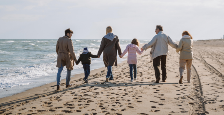 Impact image - Grandparents, parents and kids walk hand-in-hand on the beach.